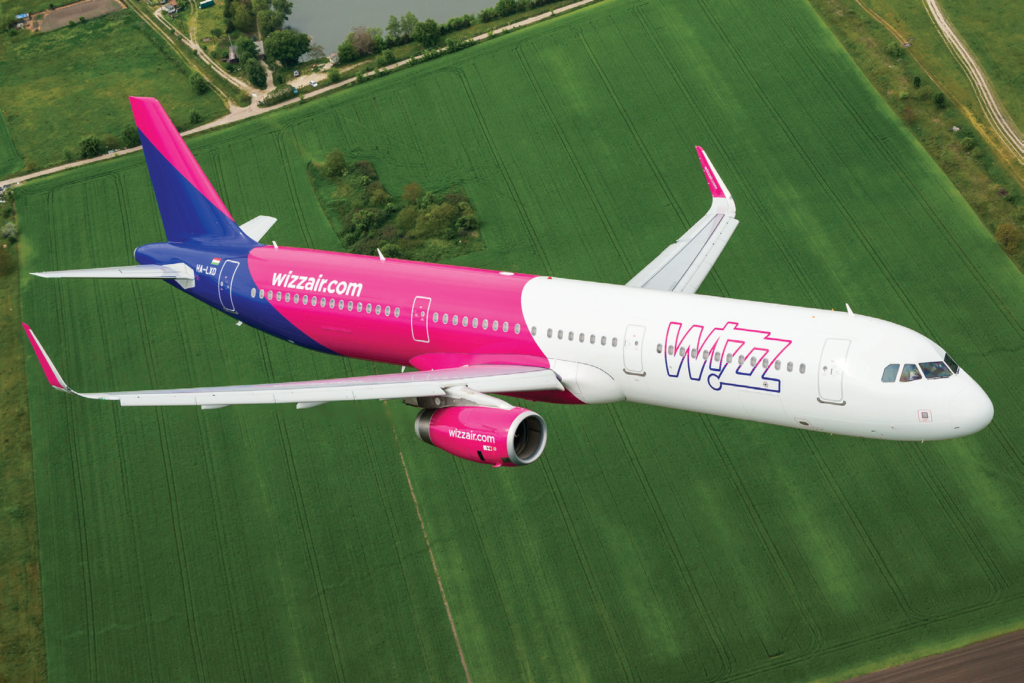 Wizz Air airplane in the air over fields